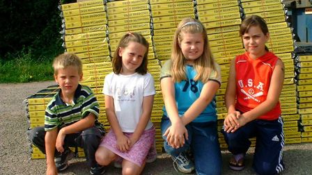 Children with a pile of old Yellow Pages, launching a recycling drive with Ipswich Borough Council i