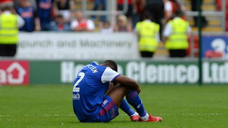 Janoi Donacien sits on the pitch disappointed following the 1-0 defeat at Rotherham towards the star