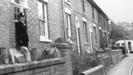 A policeman stands outside the house where the bodies of three children were found impaled on garden