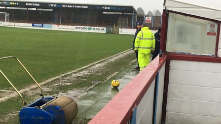 Groundstaff and roller are at the ready, but the standing water by the touchline is clear evidence o