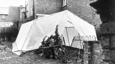A tent erected by police hides part of the iron fence where the bodies of three young children were