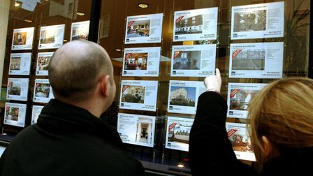 A young couple studying property for sale in an estate agents window. For many, homes are unafordabl