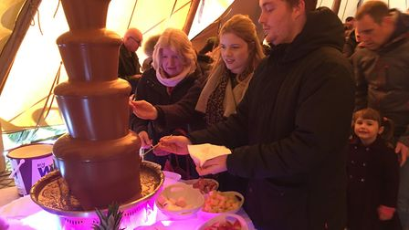 People dipping into the chocolate fountain at the Chocolate Festival in Bury St Edmunds. Picture: RU