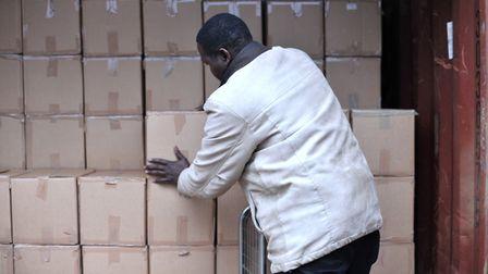 Yinka Bagbenro packing the boxes into the container Picture: SARAH LUCY BROWN