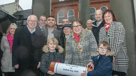 Mayor of Ipswich Jane Riley and Damon and Riley O'Donnell prepare to place the time capsule beneath