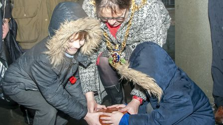 Mayor of Ipswich Jane Riley and Daman and Riley O'Donnell lower the time capsule into place under Co