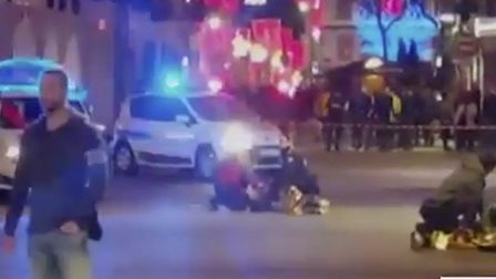In this image made from video provided by CMM, people lay on the ground after a shooting at a Christ