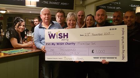 Michael Palmer with wife Debbie along with regulars at the Bennet Arms and their cheque for £1,000.