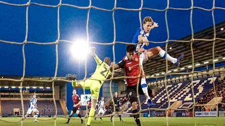 Frankie Kent is locked together with Josef Yarney, after trying to get his head to the ball, which h