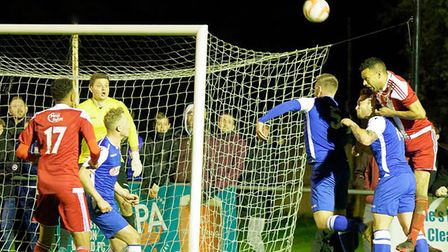 Felixstowe's Dan Davis (Right. In red) rising high to break Coggeshall defence during last season's