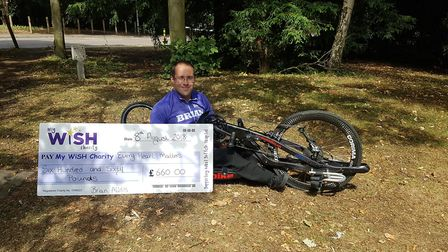 Brian Alldis with his cheque for £660 following his hand cycle ride. Picture: MYWISH CHARITY