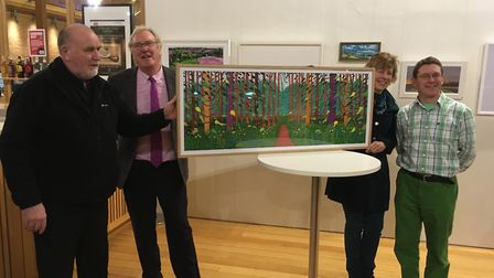Melanie Lesser proudly displays her David Hockney reproduction print with, from left to right, Marty