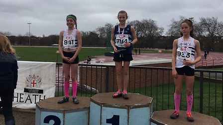 Ruby Vinton, middle, stands on top of the podium after winning the South of England under-13 title,