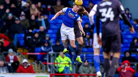 Matthew Pennington rises high and wins the ball in this battle with Steven Fletcher. Picture: STE