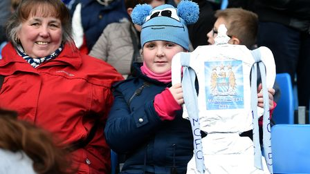 A Manchester City fan in the stands with a home made FA cup trophy. Don't tell her it's all about th