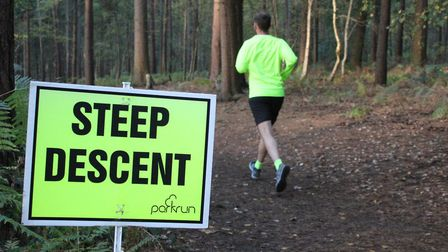 The sign warning runners of a steep descent ahead, through the trees during the Rushmere parkrun. Pi