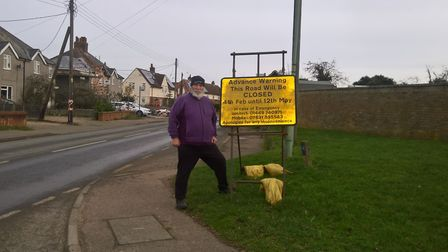 Elmswell parish councillor Mike Friend standing next to a sign letting people know that Wetherden Ro