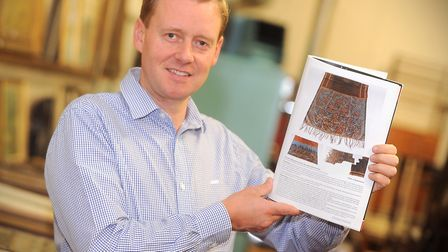 Ed Crichton from Lacy Scott and Knight in Bury St Edmunds holding up the catalogue showing the Jack