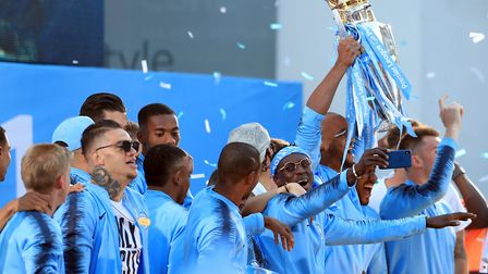 Manchester City players celebrate with the Premier League trophy during the Premier League champions