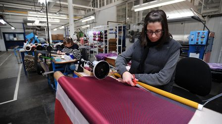 A worker at Vanners Silk in Sudbury inspects and rolls fabric Picture: PHIL MORLEY