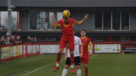Needham's Luke Ingram takes to the air to win a header against Royston. Picture: BEN POOLEY