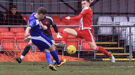 Lewis Smith (blue) fires home the opening goal for Tilbury despite the attempted block by Seasiders
