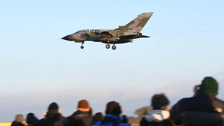 Plane spotters watch as one of three RAF Tornado GR4 aircraft with a specially painted livery to com
