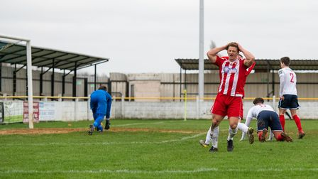 Felixstowe striker Liam Hillyard turns away in disbelief as his strike canons off the upright into t