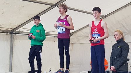 Ben Peck, centre, stands on top of the podium after winning the under-13 title at the Inter-Counties