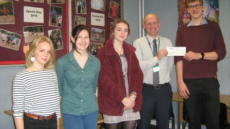 Simon Rolfe, head of commercial at Persimmon Homes, presenting a cheque for £500 to sixth form stude