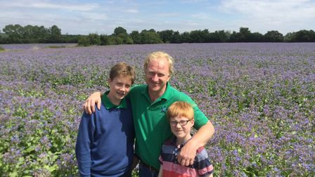Andrew Fairs with sons, Charlie, left, and Thomas in a field of borage at his farm at Great Tey Pic