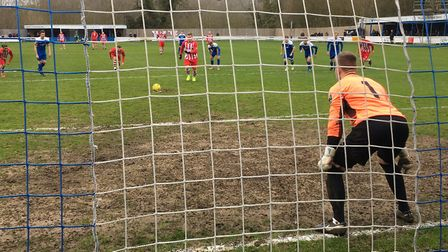 Bury keeper Luis Tibbles gets ready as Bowers & Pitsea striker David Knight steps up to take a penal