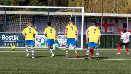 Witham's Chinedu Vine (far right) sends Paul Walker the wrong way to open the scoring against AFC Su