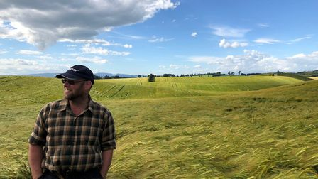 Graham Thompson reviewing a field of Barley with 15 other farmers from the UK during a trip to look