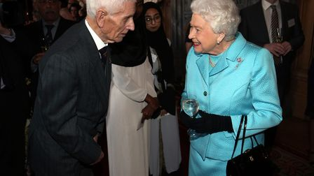 Queen Elizabeth II meets West Suffolk Hospital volunteer Ron Knight at a reception to mark the cente