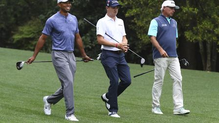 Tiger Woods, Justin Thomas, and Fred Couples walk down the 11th fairway to Amen Corner representing