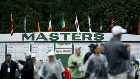Fans arrive for a practice round that was under a weather warning at the Masters golf tournament on