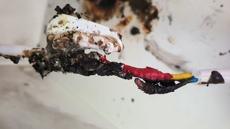 A picture showing the faulty piece of wiring at the back of a washing machine which caused the fire