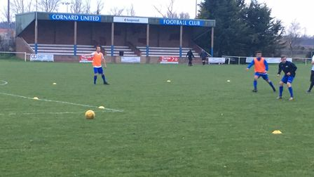Players warm up before Tuesday night's match at Great Cornard, with the main stand in the background