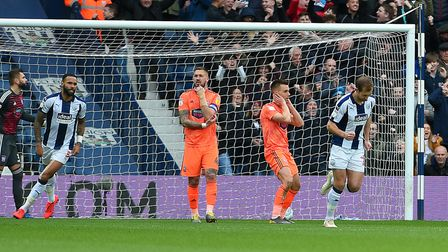 Jonas Knudsen holds his head after he deflected an early West Brom free-kick into his own net. Photo