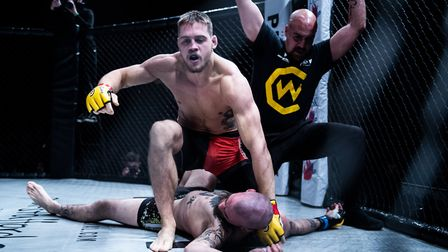 Craig Edwards rises to celebrate after submitting Scott Butters in their lightweight clash at Cage W