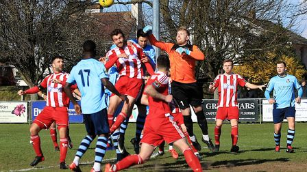 Bowers& Pitsea keeper Andrew Wilton punches clear under pressure from Seasiders Joe Francis Photo; S
