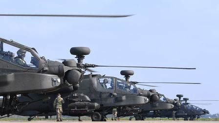 Final checks are carried out on five Apache helicopters on the flight line at Wattisham Airfield in