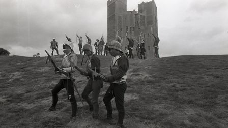 Reinactors pose with their weaponary, archers lined up at the ready in the background Picture:OWEN
