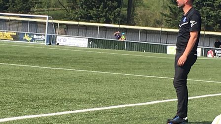 Bury Town manager Ben Chenery watches on, in the sunshine, as his side take the initiative at AFC Su