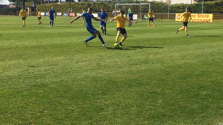 Mildenhall Town's Tommy Robinson (yellow) competes for the ball during the Bostik North clash with C