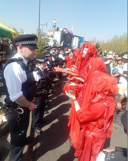 Red walkers from Extinction Rebellion blocking the path of the Metropolitan Police on Waterloo Bridg