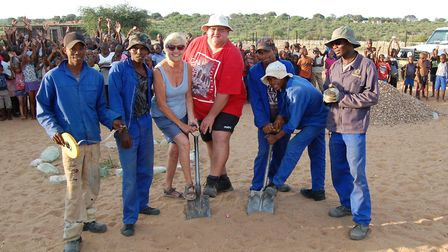 Linda Bullen starts digging the foundations of the multi-purpose hall with builder Riaan Potieger, h