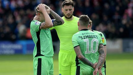 So near and yet so far: Colchester United players show their disappointment after missing out on the