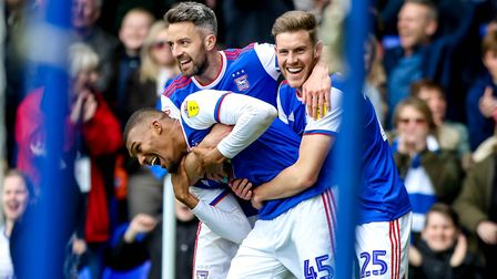 Collin Quaner is hugged by Callum Elder and Cole Skuse after scoring late in the 3-2 victory over Le